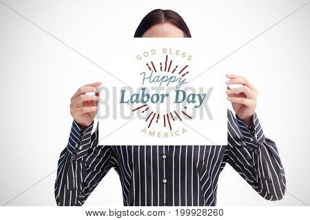 Smiling woman showing a big business card in front of her face against digital composite image of happy labor day and god bless america text
