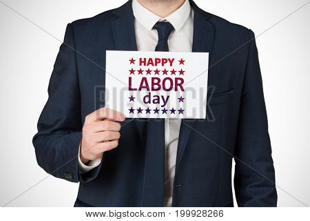 Businessman showing card to camera against poster of happy labor day text