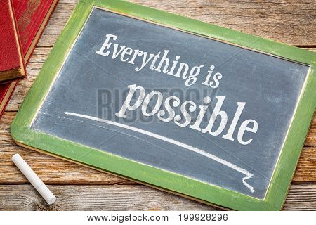 Everything is possible sign - a slate blackboard with a white chalk and a stack of books against rustic wooden table