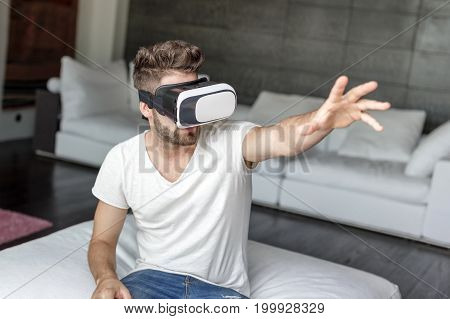 Young man playing virtual reality by VR glasses at home