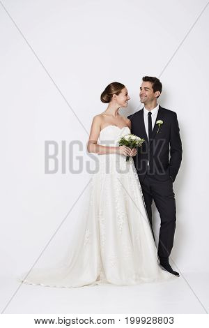 The handsome newlywed couple standing in white studio
