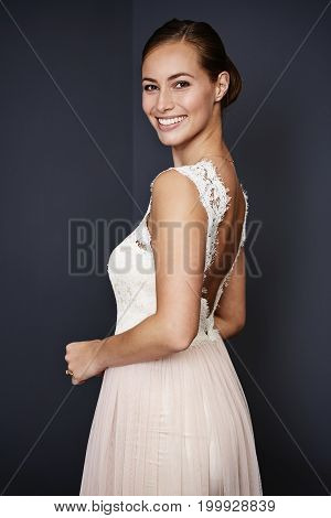 Beautiful ballgowned brunette smiling at camera studio