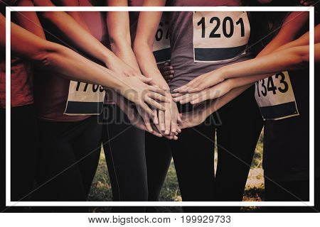 Portrait of female breast cancer marathon runners stacking hands in park