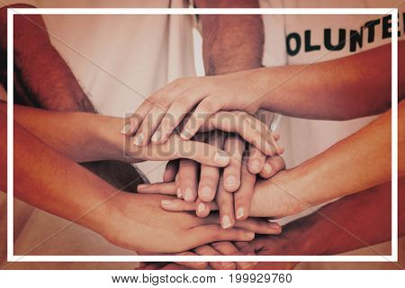 Mid section of volunteers stacking hands on white background