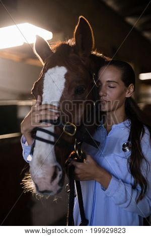 Close up of female vet with eyes closed standing by horse at stable