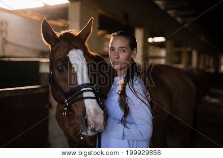 Portrait of confident female vet standing by horse in stable