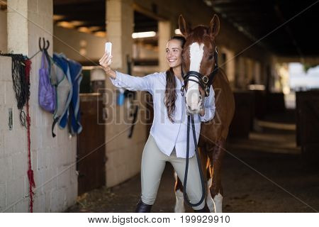 Female vet taking selfie with horse in stable