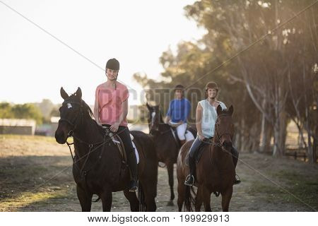 Portrait of women with trainer riding horse at barn