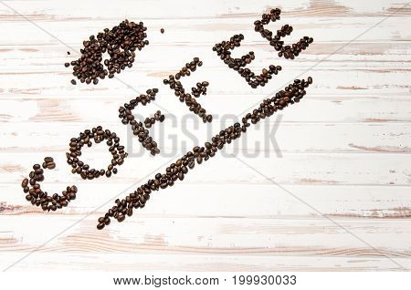 The word coffee written with fresh coffee beans with some extra coffee on a white wooden table