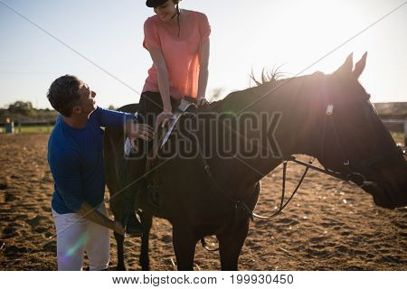 Male trainer adjusting young woman leg on stirrup at barn