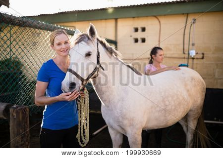 Young female friends standing by horse at barn