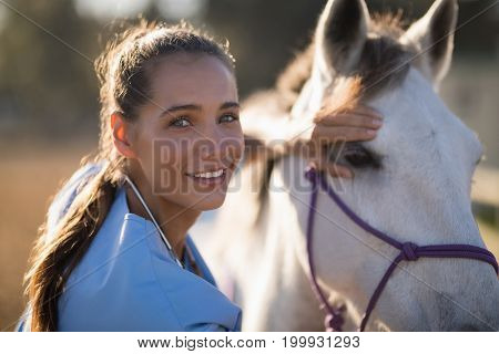 Portrait of smiling female vet checking horse at paddock during sunny day