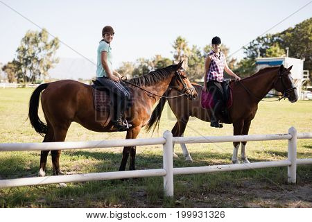 Portrait of female friends horseback riding at field during sunny day