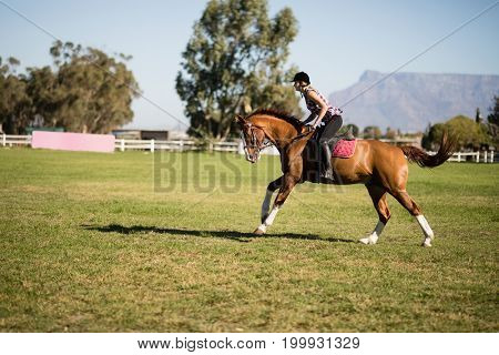 Side view of female jockey horseback riding on field during sunny day