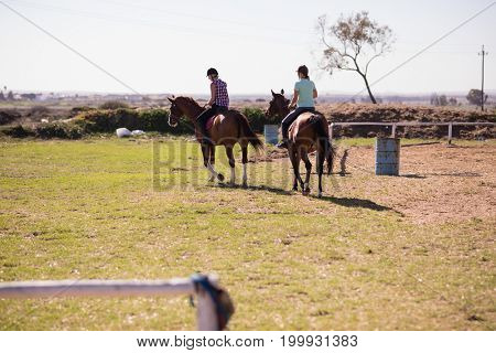 Rear view of female friends horseback riding on field at paddock