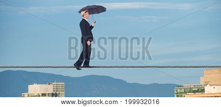 Businessman with umbrella walking on white background against buildings in city against blue sky