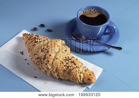 Croissant with flax seeds and cup of hot coffee for breakfast on blue table