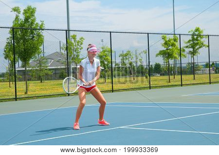 Young woman in white dress playing tennis on the tennis court