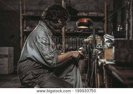 The worker in the workshop processes the metal part under the light of a light lamp