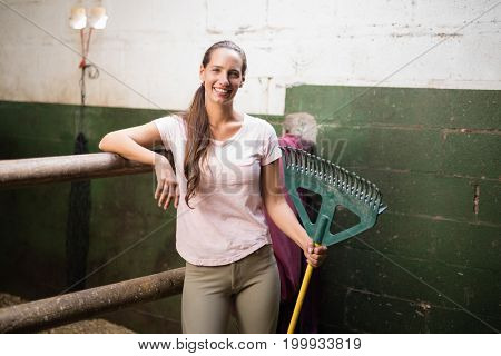 Portrait of smiling female jockey  holding rake while standing by wall in stable
