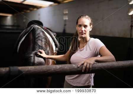 Portrait of young female jockey standing by horse in stable