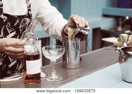 Bartender is pouring infusion into a mixing glass, toned image