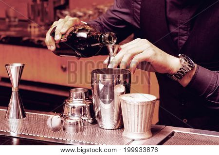 Bartender is pouring alcohol into a mixing glass, toned image