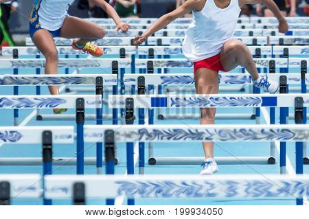 Two high school girls are racing the 100 meter hurdles on a blue track outdoors on a sunny afternoon. poster
