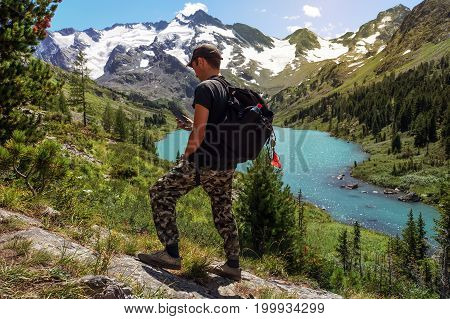 Hiker with backpack standing on a hillside and looking in the navigation on smartphone in the background beautiful mountain landscape with turquoise lake.