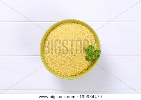 bowl of raw couscous on white wooden background