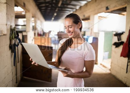 Smiling female jockey using laptop while standing in stable