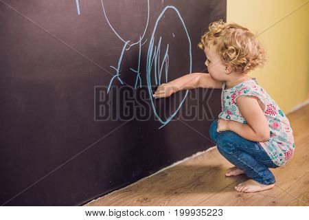 Girl Toddler Paint With Chalk On A Blackboard
