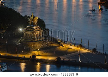 View of Deutsches Eck with the statue of the emperor William I in Koblenz Germany with Rhine and Moselle River in the night.
