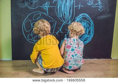 Boy And Girl Paint With Chalk On A Blackboard