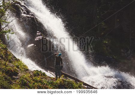 Hikers Man Backpacker Looking At A Waterfall In The Forest.