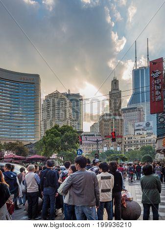 Shanghai, China - Nov 6, 2016: Crowds on Nanjing Road Pedestrian Street enjoying late afternoon dramatic cloudscape.