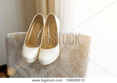 Wedding shoes on the back of the armchair near the window.