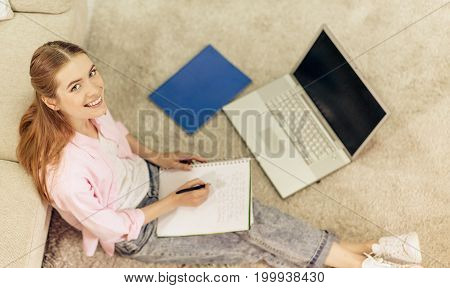 Smiling young girl sitting on floor at home studying, Female on carpet at home writing in notebook.