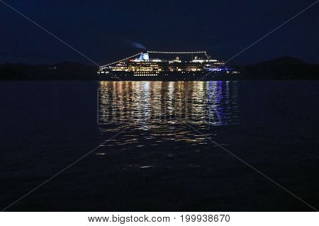 A cruise ship sailing down the Norwegian coast at night shining with lights.