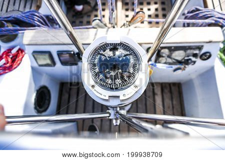 A compass a view from above the steering wheel on a yacht.