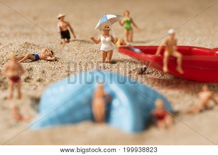 some different miniature people wearing swimsuit relaxing next to a blue plastic starfish and a red toy shovel on the sand of the beach