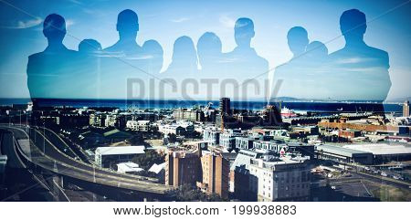 Silhouettes standing against cityscape against sky