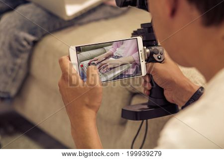Man shooting girl typing on laptop with cell phone camera. Close up view of shot on mobile phone.