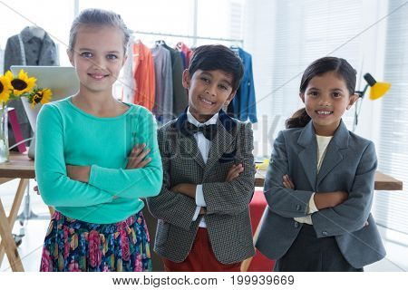 Portrait of happy business people with arms crossed standing in office