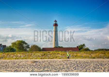 September 6 2014: Cape May New Jersey A tourist hauls her beach gear in front of the Cape May lighthouse in the evening light.