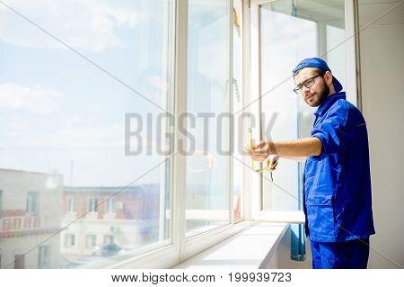 Window installation worker measuring window with tape