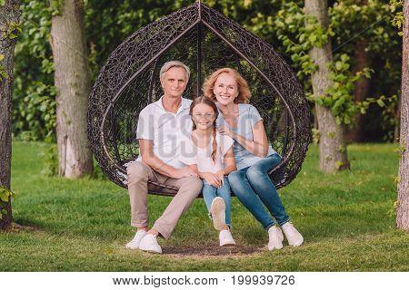 Grandparents And Granddaughter In Garden