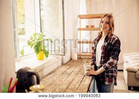 Attractive young girl standing close to window with cup of coffee or tea. Female at home in casual clothes drinking coffee enjoying staying at home.