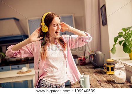 Young attractive girl listening music in headphones at home. Female enjoying music standing close to window near wooden desk.