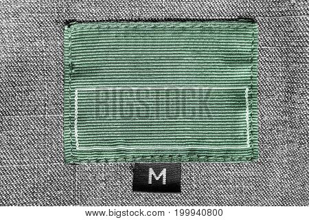 Green textile clothes label on gray tweed background closeup